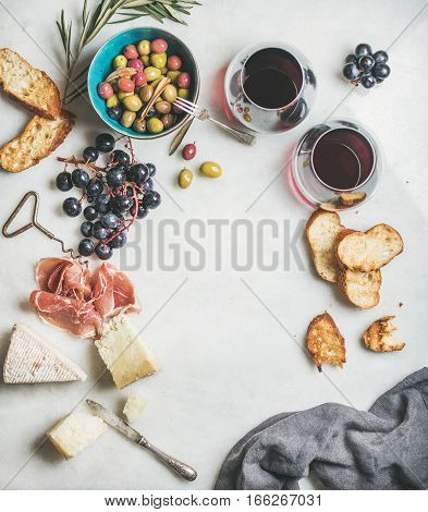 Wine and snack set. Variety of cheese, olives, prosciutto, roasted baguette slices, black grapes and glasses of red wine over grey marble background, top view, copy space
