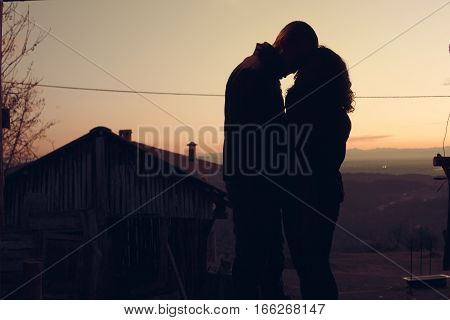 Warm embrace of the happy couple in love at sunset. People in love Timeshares Romantic Kiss - Kiss a romantic sunset share an embrace enjoy the sun and the beautiful natural mountain young couple in love.