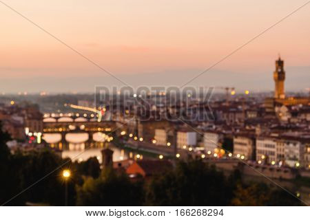 Blurred unfocused panoramic view to the river Arno with Ponte Vecchio Palazzo Vecchio and Cathedral of Santa Maria del Fiore (Duomo) at dusk time. Florence Italy