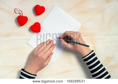 Woman writing love letter card for Valentines day top view of female hands retro toned