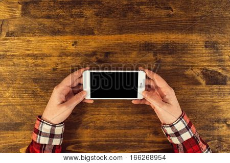 Casual female graphic designer using smart phone top view of office desktop