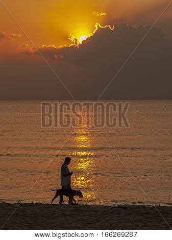man walking with a dog on a beach with sunset