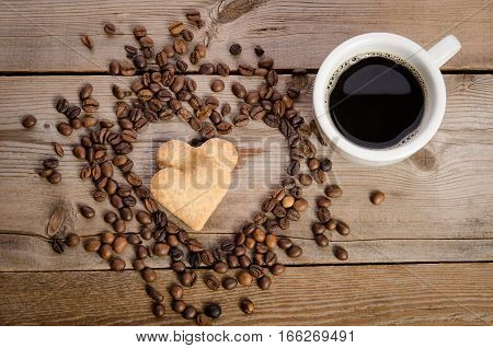 The Cup Of Coffe And Frame- Heart From Coffee Beans And Two Cookies-heart  Inside It On  Wooden Tabl