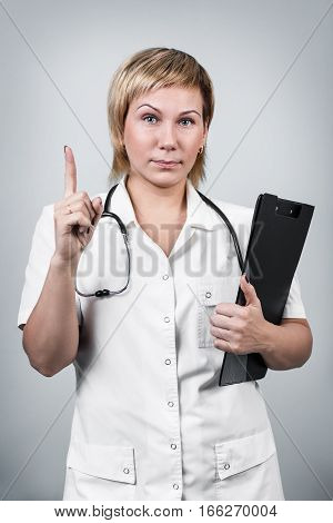 Female doctor showing a warning gesture over gray background