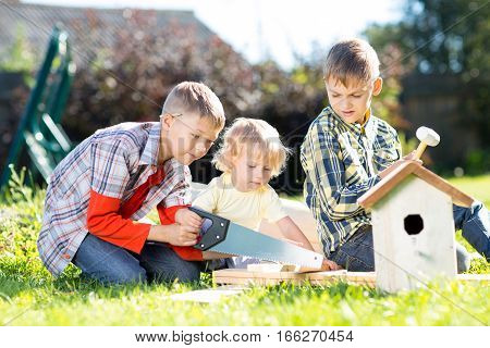 Kids making together nesting box outdoors. Older boy teaches his younger brother handicrafts