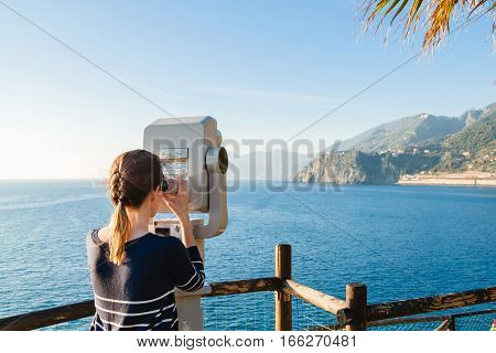 Young Girl Looking Through A Coin Operated Binoculars On The Sea Shore Of Cinque Terre, Liguria, Ita
