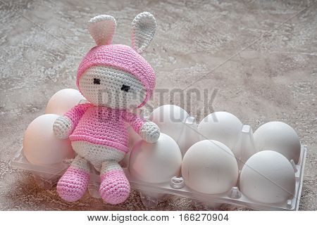It's time to paint Easter eggs. Preparation for the celebration. Composition with a box full of white unpainted eggs the site of one of the eggs sitting pink handmade amigurumi toy bunny.