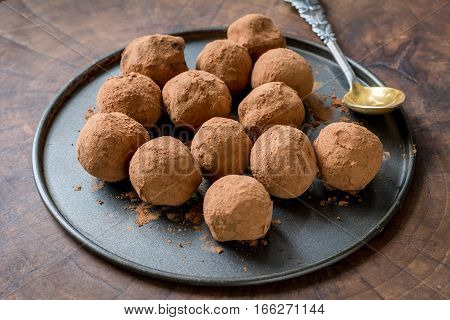 Chocolate truffles rolled with cocoa powder on a plate over wooden background.