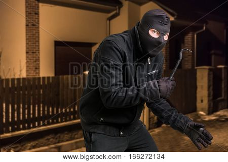 Masked Thief In Balaclava With Crowbar Wants To Rob A House