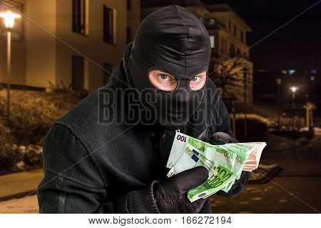 Masked Thief In Balaclava With Stolen Money