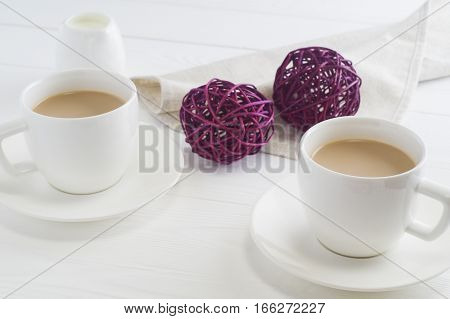 Romantic breakfast with couple white cups of coffee on white wooden background. Cocoa or coffee with milk close up. The concept of a romantic encounter.