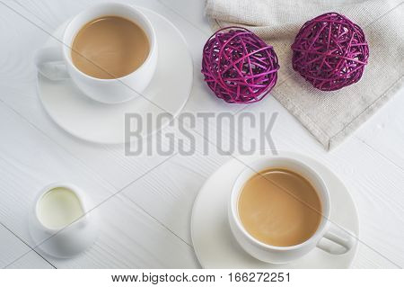 Romantic breakfast with couple white cups of coffee on white wooden background top view. Cocoa or coffee with milk. The concept of a romantic encounter flat lay.
