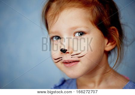 Baby 3 years with face painting of a cat, meowing and smiling