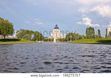 ASTANA, KAZAKHSTAN - July 14, 2016: Pyramid - Palace of Peace and Accord with water on foreground