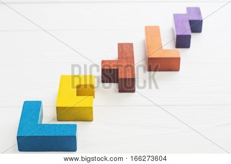 Abstract Background. Different shapes wooden blocks on white wooden background. Geometric shapes in different colors. Concept of creative logical thinking or problem solving. Copy space.