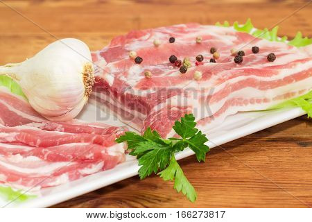Uncooked partly sliced streaky pork belly bacon with spice garlic and greens on a white dish closeup on a old wooden surface