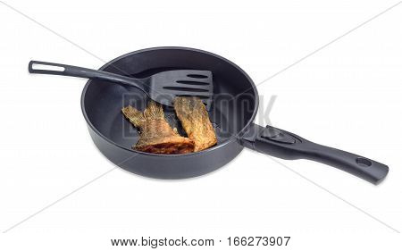 Fried tail portion and other slice of carp and plastic spatula on an aluminium cast frying pan with ceramic non-stick coating on a light background
