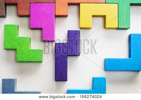 Abstract Background. Different colorful shapes wooden blocks on beige background background close-up. Geometric shapes in different colors. Concept of creative logical thinking or problem solving.