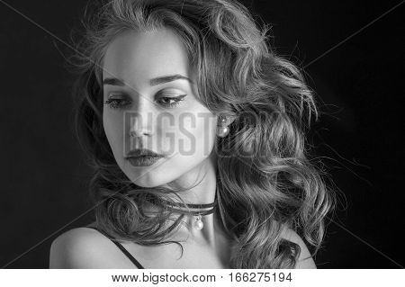 luxury woman with curly long hair on black background, monochrome