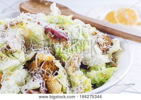 Caesar Salad with on white plate. Delicious Caeser salad with croutons roasted chicken meat parmesan cheese and cos lettuce with sauce healthy recipe close-up. Healthy food.