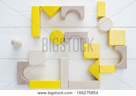 The yellow-beige maze of wooden blocks of various shapes top view. Man standing in front of the maze flat lay. Difficult path to find exit business concept. The concept of a strategy search for solutions.