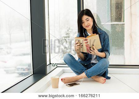 Asian Woman Reading A Book Next To Big Windows