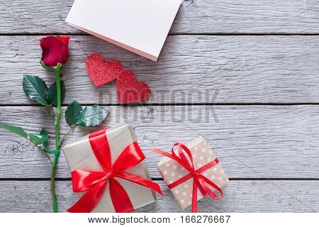 Valentine background with red rose flower, handmade paper hearts and present box on rustic wood. Happy lovers day gift mockup, copy space