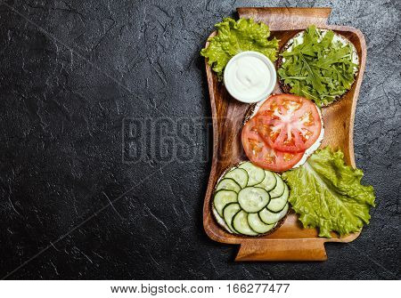 Vegetarian sandwiches with cream cheese and vegatables on black background, top view