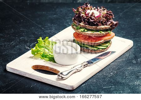Vegetarian sandwiches with cream cheese and vegatables on black background