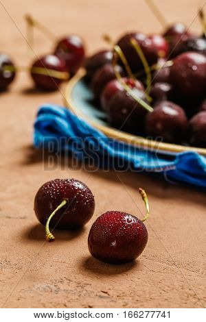 Cherries in a bowl with water drops close up on brown background