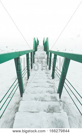Stairs to nowhere concept. green railings and steps in snow. View to white space. Vertical picture.