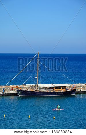 AGIOS NIKOLAOS, CRETE - SEPTEMBER 17, 2016 - Yacht moored in a small harbour at the rear of the Hotel Mirabello with a tourist on a paddle board in the foreground Agios Nikolaos Crete Greece Europe, September 17, 2016.