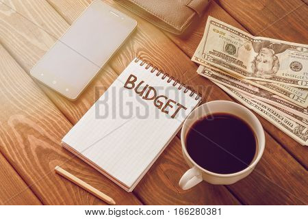 Budget planing concept. Notepad with word Budget, mobile phone, money, pouch and coffee on wooden table. Vintage style. Retro toned picture.