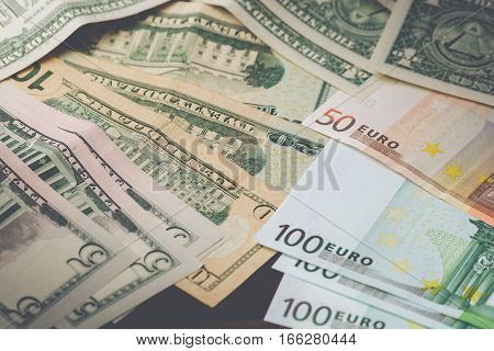close up view of cash money dollars bills and euro banknotes on table.