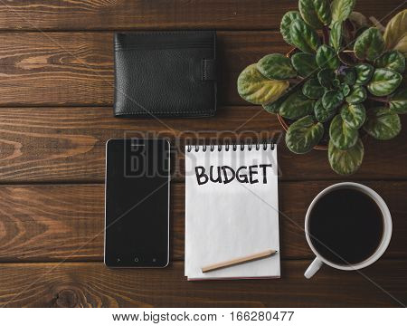 Budget planing concept. Top view of notepad with word Budget, mobile phone, cup of coffee, pouch and table flower on wooden background. Vintage toned picture.