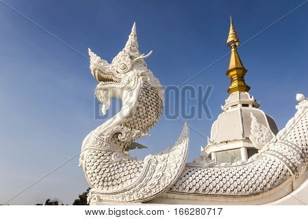 stone serpent king of Nagas near the river in blue sky