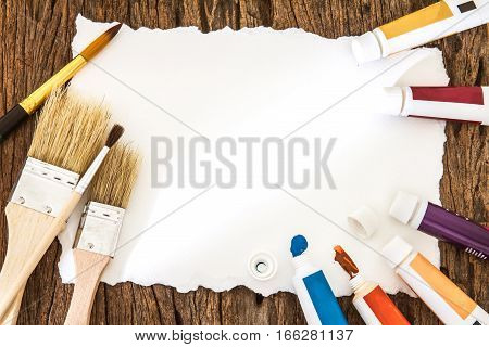 Art brush watercolor paint with white paper art on wooden background