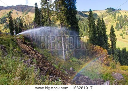 Woman Are Standing In The Mountains Near A Water Pipe With Rainbow. Tien Shan Mountains, Almaty, Kaz