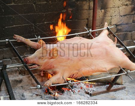 Big Pig On The Spit And Slowly Cooked On The Large Fireplace