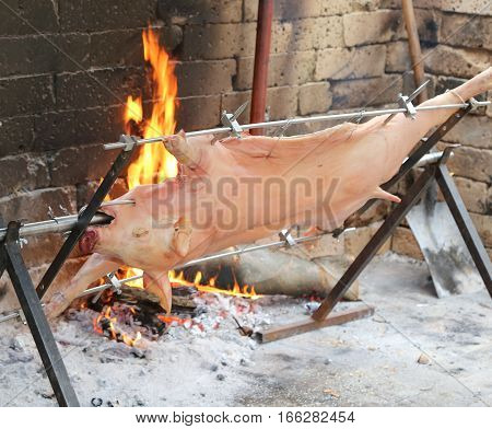 Pig On The Spit And Slowly Cooked On The Large Fireplace