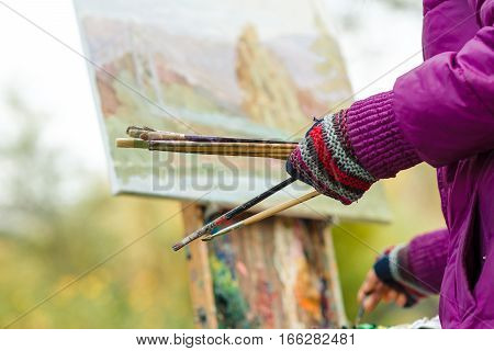 Female artist's hand hold paintbrushes and painting a sketch of the picture with oils paints in the open air.