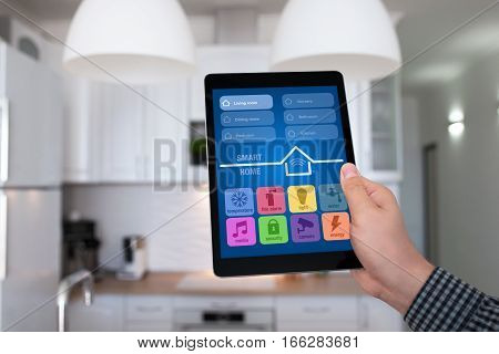 male hand holding tablet with app smart home on background kitchen in house
