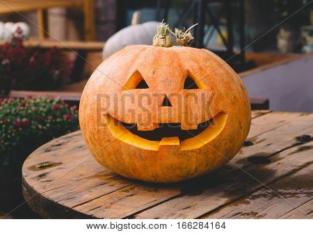 Smiling Halloween pumpkin is on a wooden table. The background is blurred