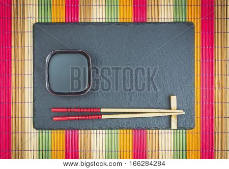 Chopsticks and soy sauce bowl on slate coaster on multicolored bamboo scroll mat. Japanese style food background. Top view with copy space