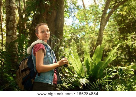 Portrait woman hiker watching through binoculars wild birds in the tropical jungle. Bird watching tours. Ecotourism concept image travel.