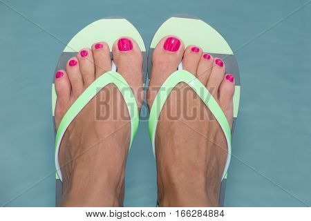 Feet With Red Nails With Green Tapers In The Pool To Symbolize The Summer