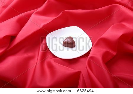 Coffee in white cup with chocolate pralines on red background.
