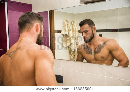 Shirtless muscular handsome man looking at himself in bathroom mirror in the morning