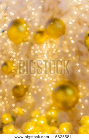 Abstract background blurred yellow golden bokeh circles and festive balls in background use for celebrating event.