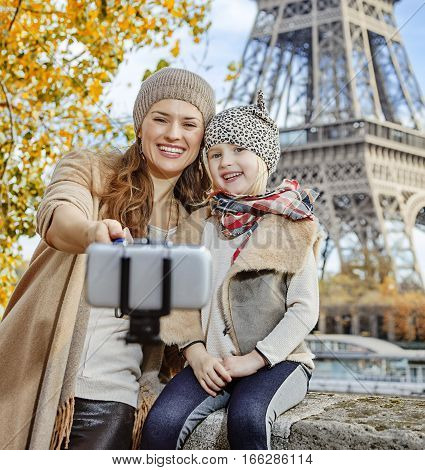 Smiling Mother And Daughter Travellers Taking Selfie In Paris